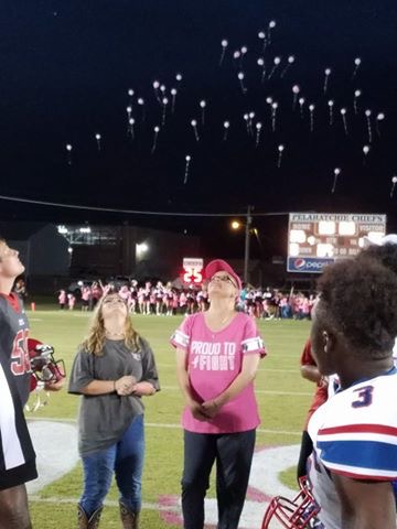 Mrs. Wendy Carter, in the middle, assisted with the coin toss at the football game.