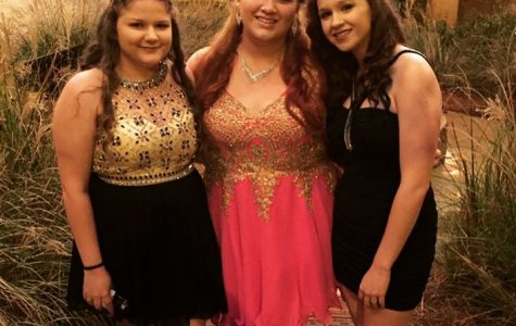 Three girls posing for their homecoming pictures.