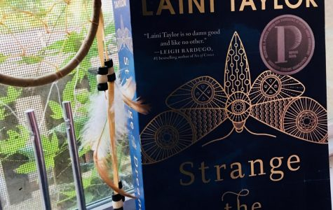 Strange the Dreamer's book cover depicts shades of blue and a intricate moth symbolizing the main female lead, Sarai.