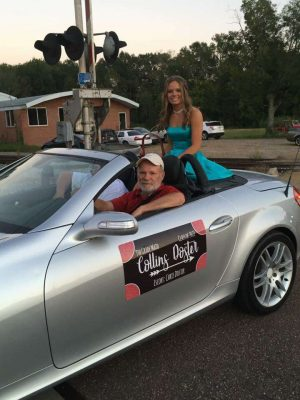 Collins Doster parades through town on her fancy car.