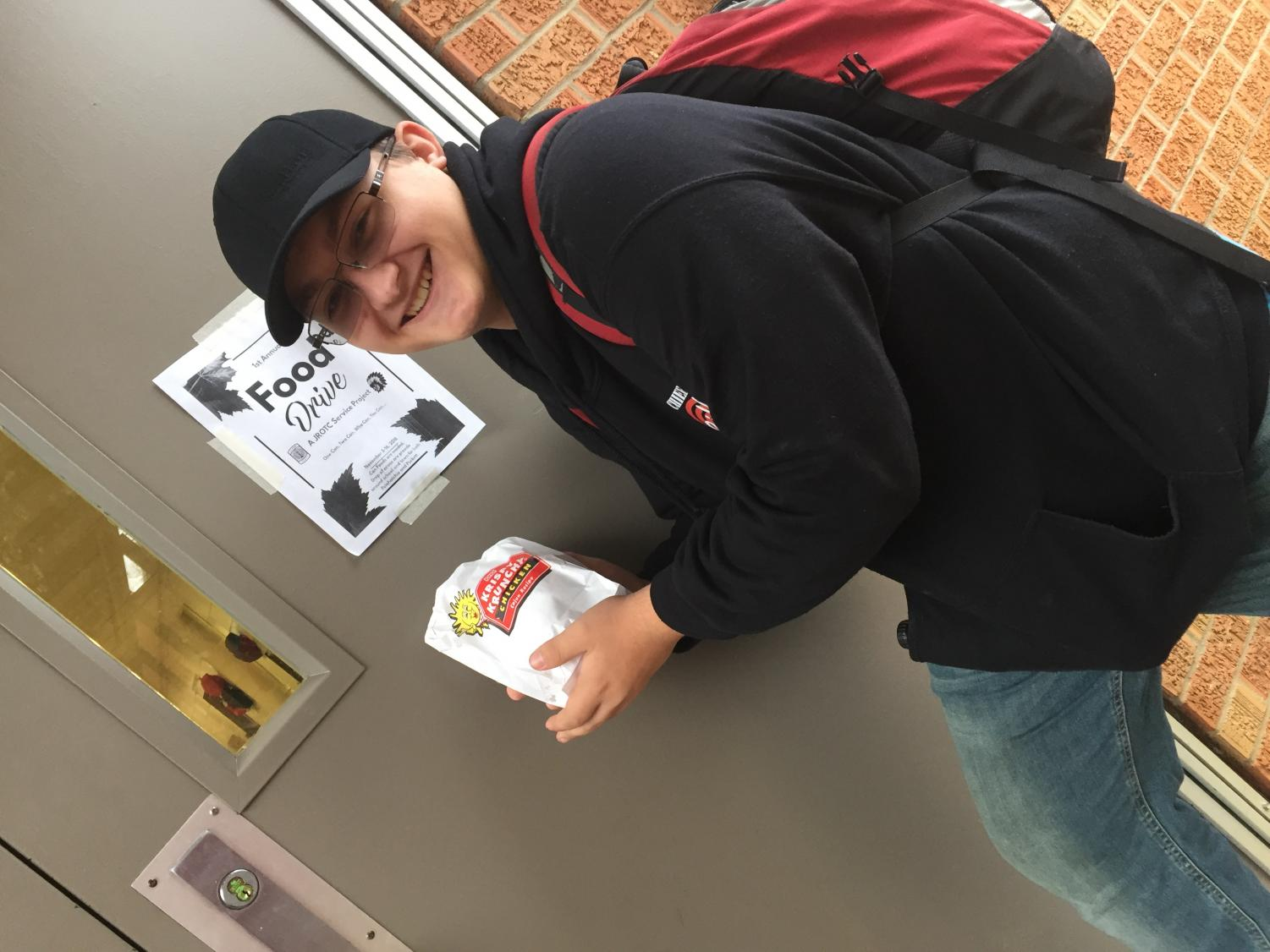 Landin Pierce holds his food in front of the Food Drive poster.
