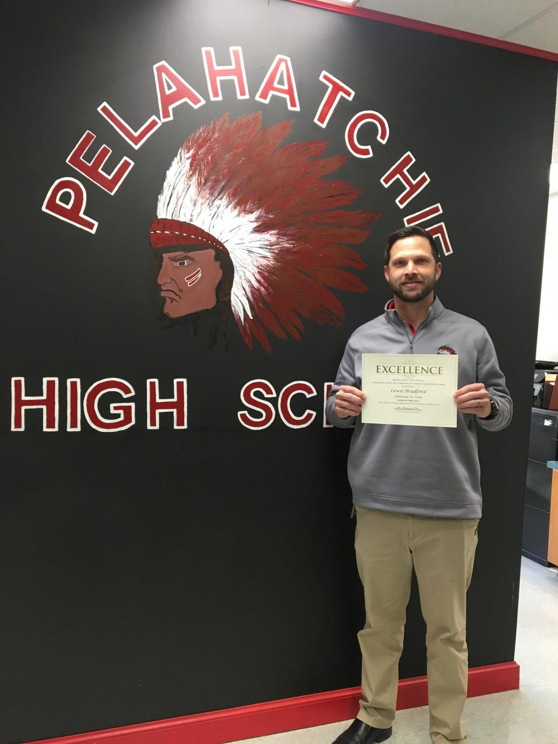 Lewis Bradford smiles proudly with his certificate for Administrator of the Month in his hand.