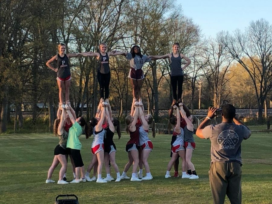 After the cheer team was unable to practice in the gym because their mats were locked up, they proceeded to practice outside. Each stunt group hit an extension and locked arms to form this picture.