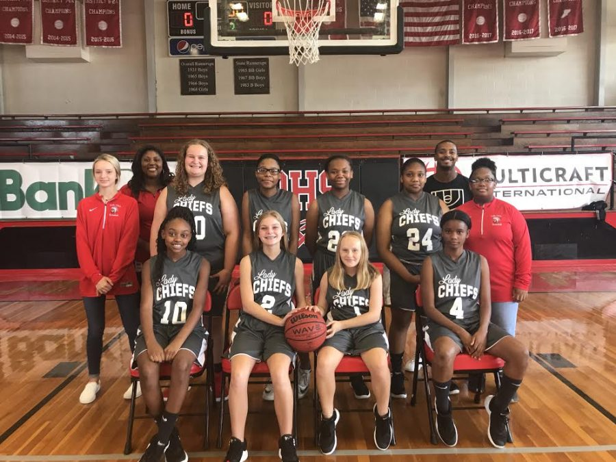 Girls Junior High basketball team pose for the camera. On the left stands Head Coach Alexis Jones and on the right stands Assistant Coach Lavadius Lyles.