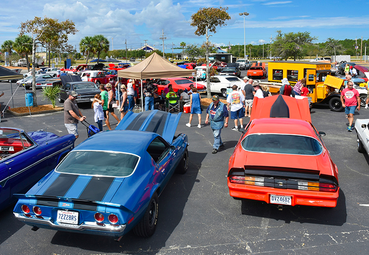 Cruisin%E2%80%99+the+Coast+attendees+observe+a+few+of+the+cars+that+were+showcased+at+the+event.%0A